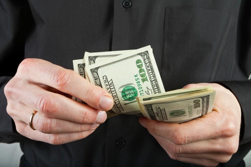 man counts money in hands dollar usa